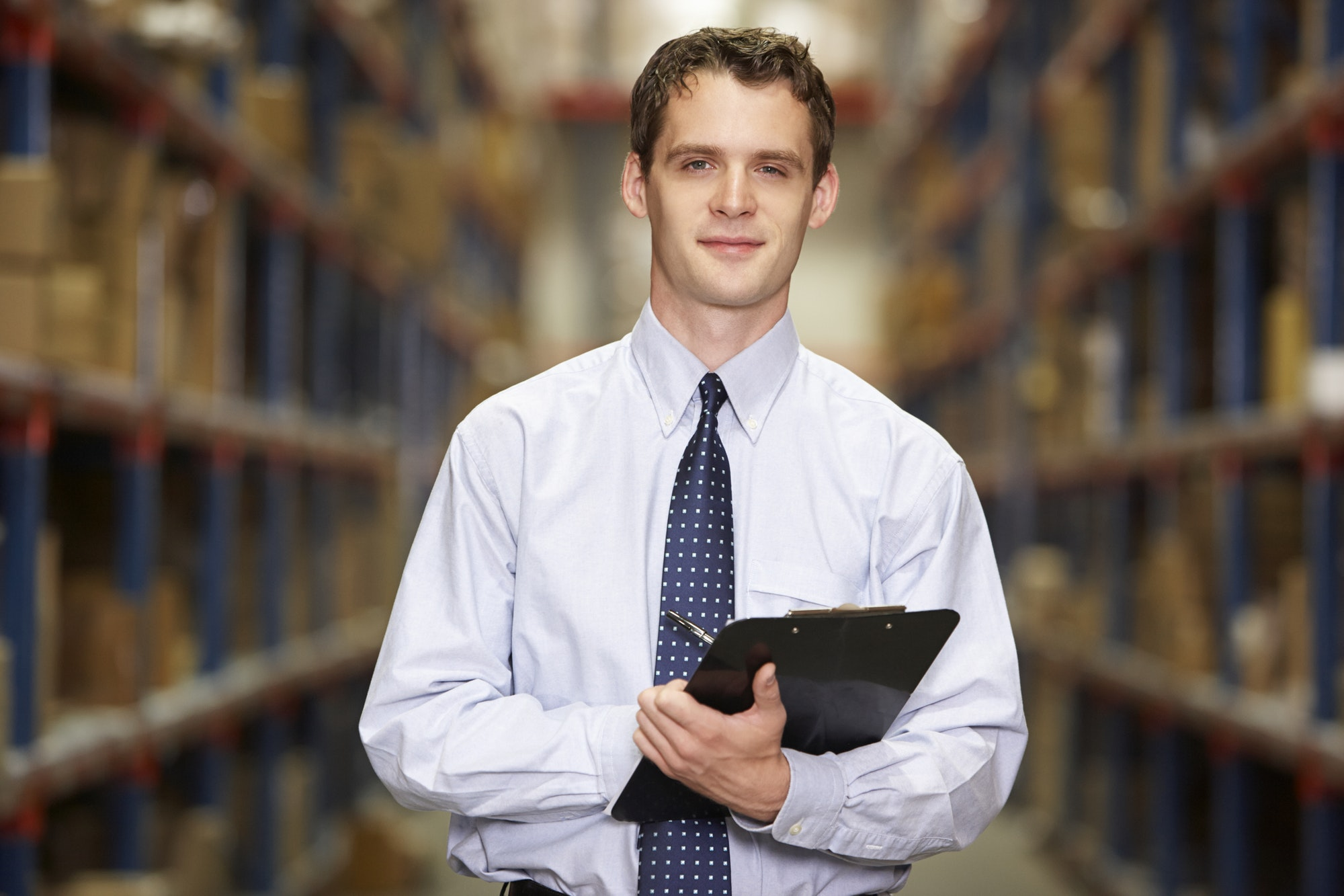 Portrait Of Manager In Warehouse With Clipboard