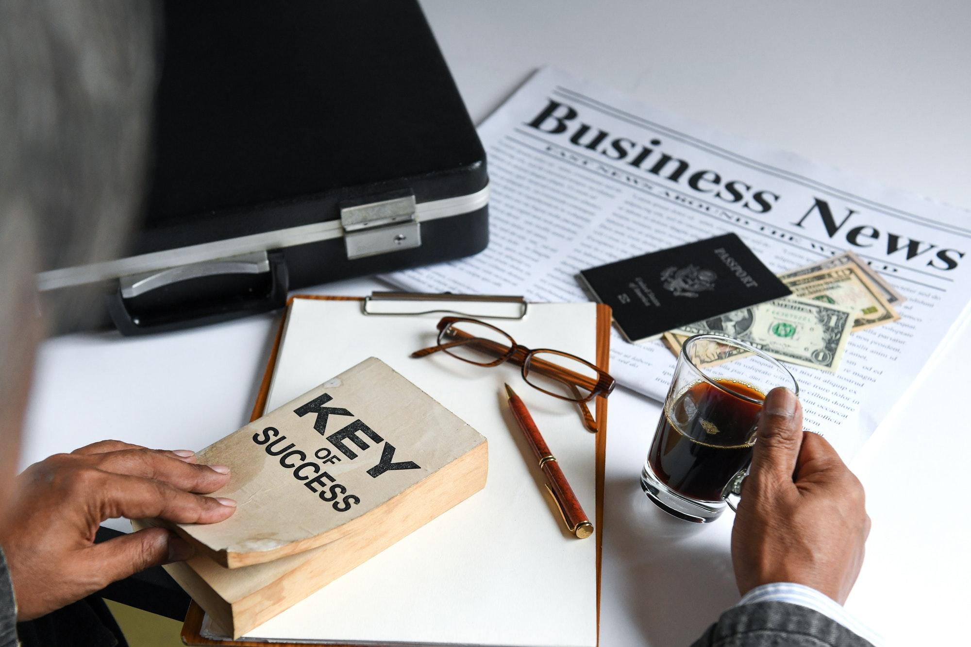ฺฺBusinessman holding coffee and key of success book.